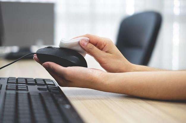 Hand des mädchens, das die computermaus reinigt.