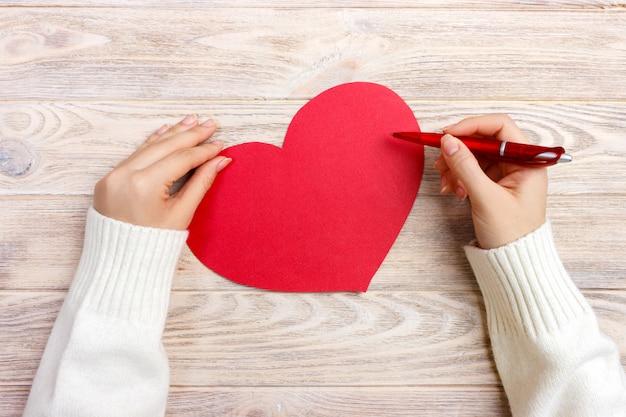 Hand des mädchenschreibensliebesbriefs am valentinstag. handgemachte rote herzpostkarte.