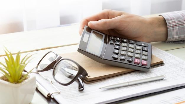 Hand des männlichen angestellten halten silbernen stift unter verwendung des taschenrechners, der ausgaben bewertet