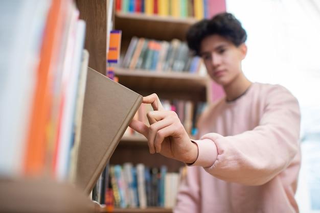 Hand des männlichen teenagers im rosa sweatshirt, das buch im braunen umschlag vom regal nimmt, während college-bibliothek nach lektionen besucht