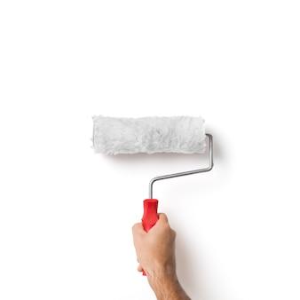 Hand des malers, der walze über weißer wand hält