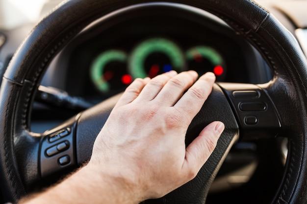 Hand des mannes auf dem rad des autos