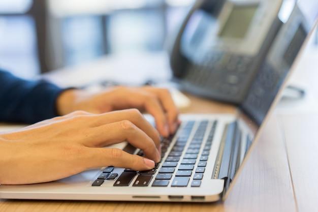 Hand des mannes auf tastatur computer tragbar