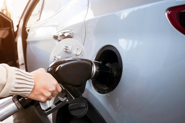 Hand des mannes das auto tanken. benzin mit kraftstoff an der tankstelle gepumpt.