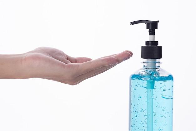 Hand des mannes, der alkoholgel anwendet, um reinigung und klare keime, bakterien, gesundheitskonzept, auf weißer wand zu machen