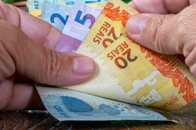 Hand des mannes, der brasilianisches geld zählt