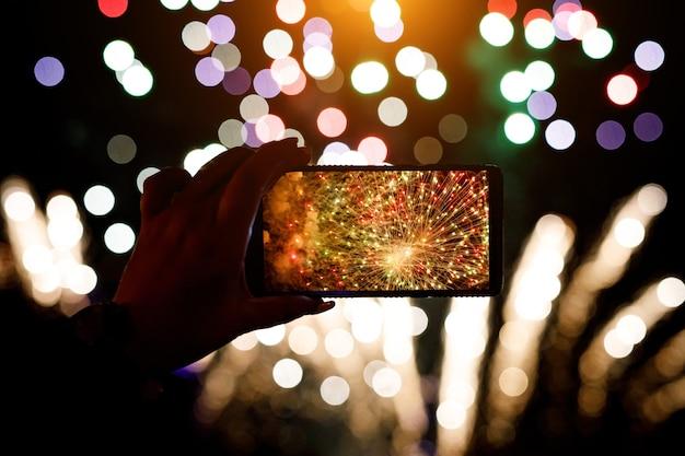 Hand des mannes, der das foto von feuerwerkskörpern mit dem smartphone macht.