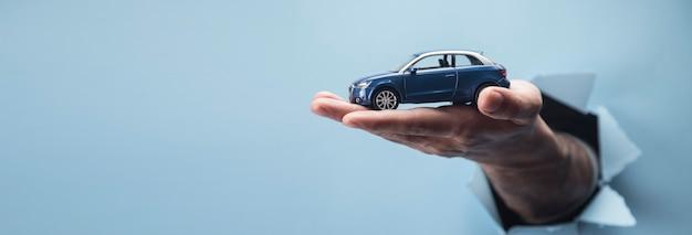 Hand des mannes, der ein auto auf einer blauen szene hält