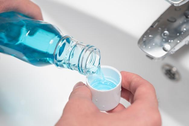 Hand des mannes, der eine flasche mundwasser in die kappe gießt.