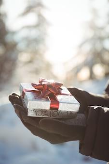Hand des mannes, der geschenk während des winters hält