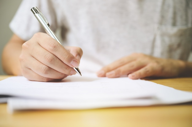 Hand des mannes, der unterschrift unterschreibt, füllt das antragsformulardokument aus