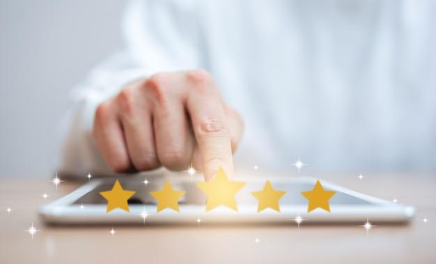Hand des mannes, die auf digitalen tablettbildschirm mit dem feedback der bewertung mit fünf sternen des goldes drückt