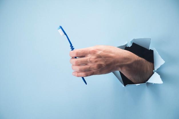 Hand des mannes, die eine zahnbürste auf einer blauen szene hält