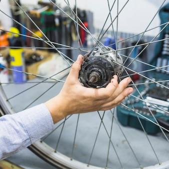 Hand des mannes, die fahrradreifen in der werkstatt repariert