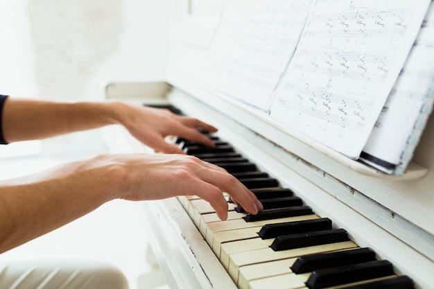 Hand des mannes, die klavier mit musikalischen anmerkungen spielt