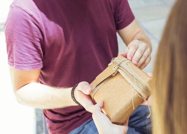 Hand des mannes, die seiner freundin geschenk gibt