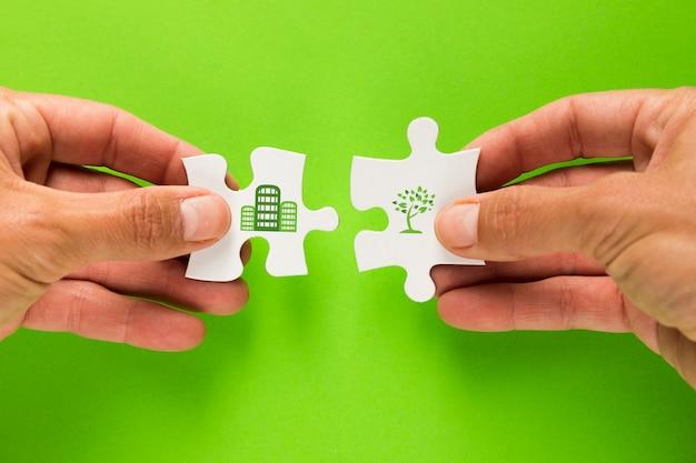 Hand des mannes, die weißem puzzlespiel mit ökologieikone über grüner oberfläche sich anschließt