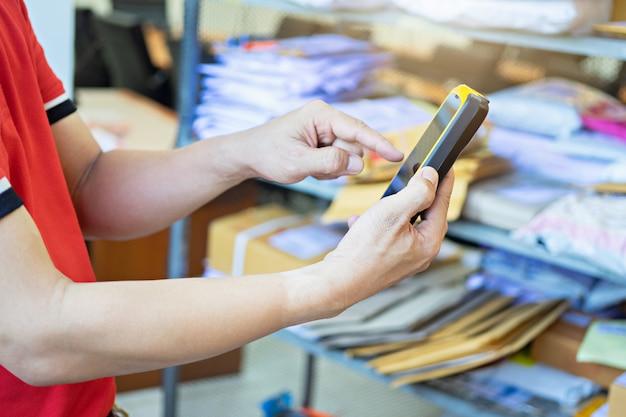 Hand des mannes einen scanner bei der anwendung für arbeit im lager berührend. arbeitskraft, die paket überprüft.