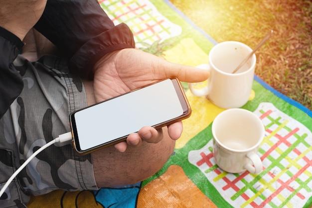 Hand des mannes halten smartphone sitzen auf matte mit zwei leeren kaffeetasse, im freien.