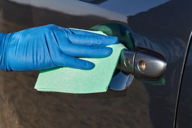 Hand des mannes im blauen schutzhandschuh wischt mit einem tuch einen außengriff der autotür ab. coronavirus- oder covid-19-schutz.