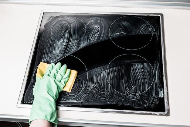 Hand des mannes im grünen handschuh, der kocher zu hause küche reinigt