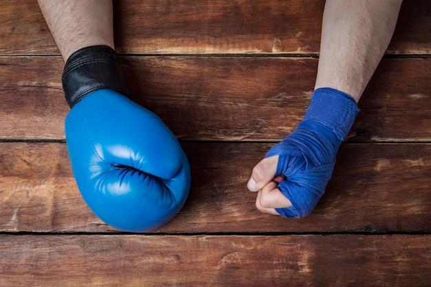 Hand des mannes in den boxverbänden und in einem boxhandschuh auf einem hölzernen hintergrund. konzept des trainings für boxtraining oder kampf.