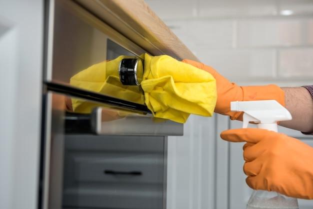 Hand des mannes in handschuhen, die den küchenofen reinigen. hausarbeit