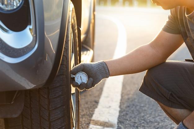 Hand des mannes luftdruck und füllende luft in den reifen seines autos überprüfend