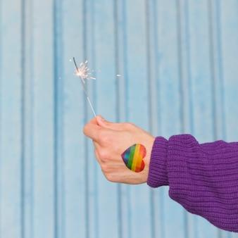 Hand des mannes mit dem regenbogenherzen, das wunderkerze hält
