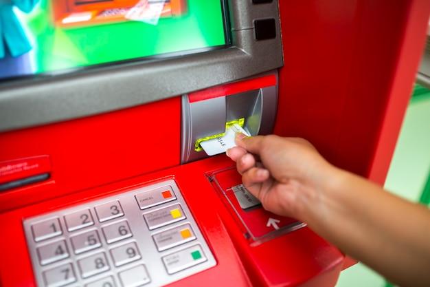 Hand des mannes mit kreditkarte, unter verwendung eines atms
