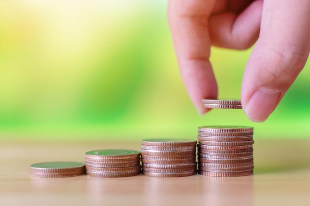 Hand des mannes münze auf wachsenden wachstumseinsparungsgeld des geldstapelschrittes setzend, konzeptfinanzgeschäftsinvestition