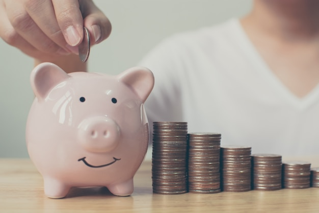Hand des mannes münzen in sparschwein mit wachsendem einsparungsgeld des geldstapelschrittes einsetzend. konzeptfinanzgeschäftsinvestition