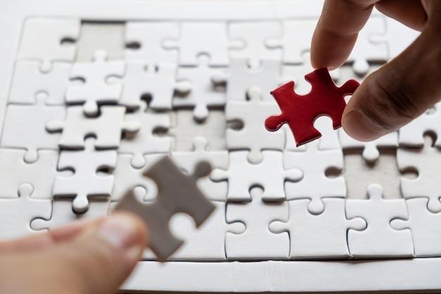 Hand des mannes oder der frau, die das puzzlen verbindet auf hölzernen schreibtisch setzt.