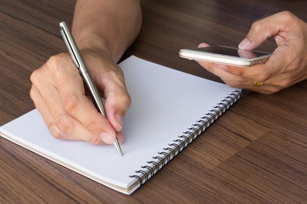 Hand des mannes schreiben und mit smartphone