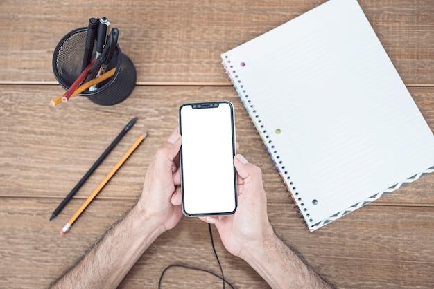 Hand des mannes unter verwendung des handys auf hölzernem schreibtisch mit briefpapier und gewundenem notizbuch
