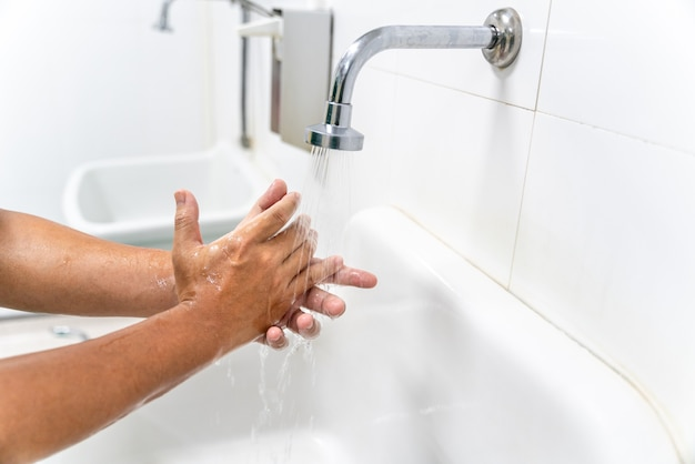 Hand des mannes waschen sie ihre hände am waschbecken mit schaum, reinigen sie die haut und lassen sie wasser durch die hände fließen. gesundheit für covid-19-präventionskonzepte