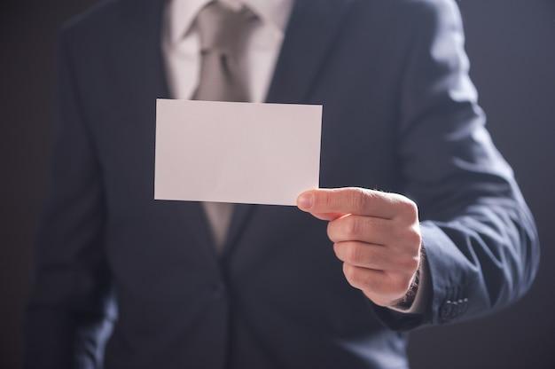 Hand des mannes zeigt visitenkarte auf dunklem hintergrund isoliert