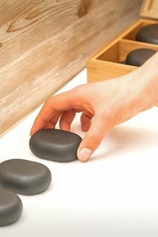Hand des masseurs mit massagesteinen auf dem tisch im spa-salon