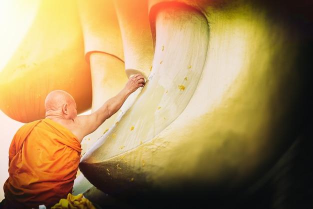 Hand des mönchwassers gießend zu großer goldener buddha-statue, songkran-festival in thailand.