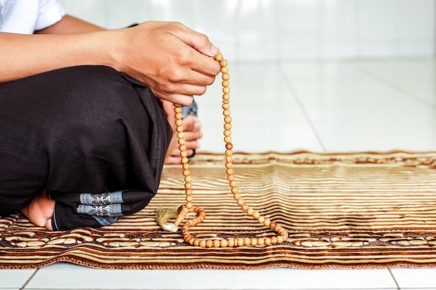 Hand des muslimischen mannes, der rosenkranz hält, um dzikir zu zählen