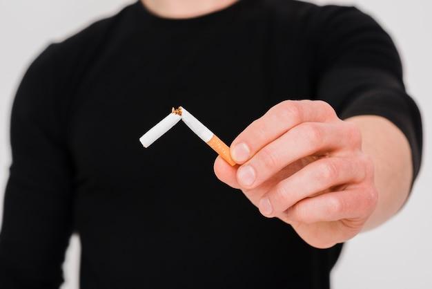 Hand des nahaufnahmemannes, die gebrochene zigarette zeigt