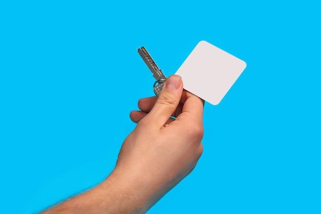 Hand des nicht wiedererkennbaren kerls hält einen schlüssel mit leerem weißen quadratischen plastikschlüsselanhänger auf metallring