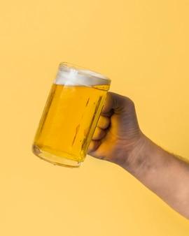 Hand des niedrigen winkels, die halbes liter mit bier hält