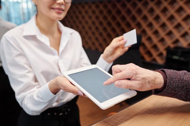Hand des reifen geschäftsmannes, der auf tablettanzeige zeigt, um seine unterschrift zu setzen, bevor karte vom hotelzimmer genommen wird