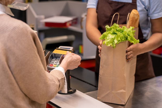 Hand des reifen weiblichen kunden, der plastikkarte über bildschirm des zahlungsautomaten durch kassiererzähler hält, während für lebensmittelprodukte bezahlt