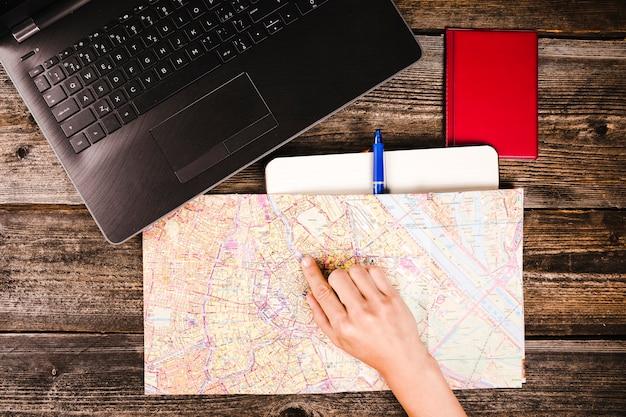 Hand des reisenden, die auf standort auf karte zeigt