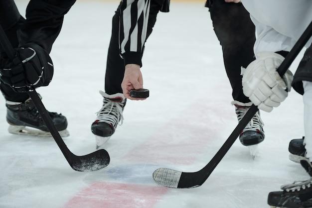 Hand des schiedsrichters, der puck über eisbahn hält, mit zwei hockeyspielern mit stöcken, die um ihn herum stehen und auf den moment warten, um ihn zu schießen