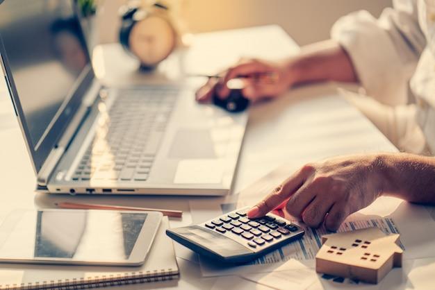 Hand des unternehmers, der zinsen, steuern und gewinne berechnet, um in immobilien und hauskauf zu investieren