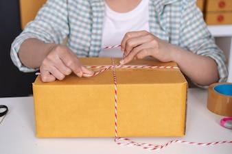 Hand des weiblichen Unternehmers binden Seile und verpacken Produkte im Paketkasten