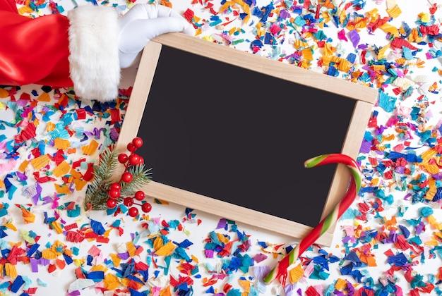 Hand des weihnachtsmanns hält geschenk auf dem hellen konfetti-hintergrund mit einkaufstafel.